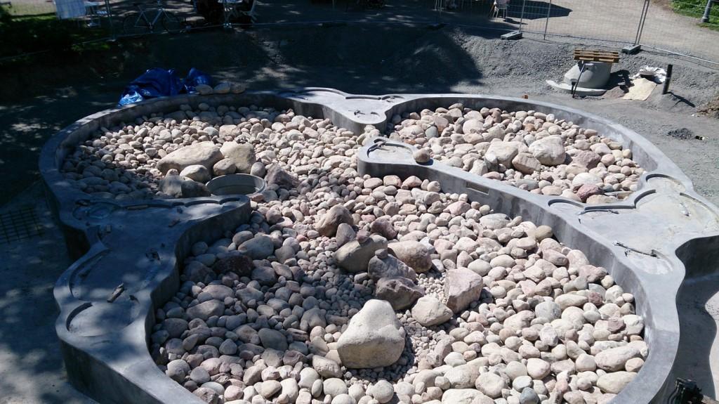 Här fyller vi dammen utanför Biotopia med sten